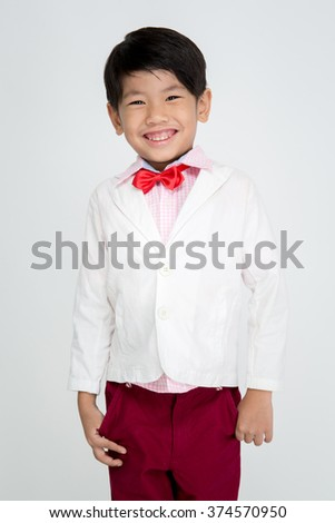 Little Asian boy in vintage white suit over gray background with smile face