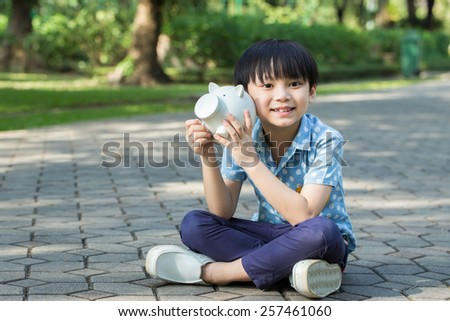 Little asian boy is sitting and holding his piggy bank in park - stock photo