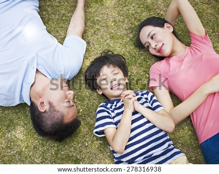 little asian boy lying on grass making a wish with eyes closed while his parents looking at him affectionately. - stock photo