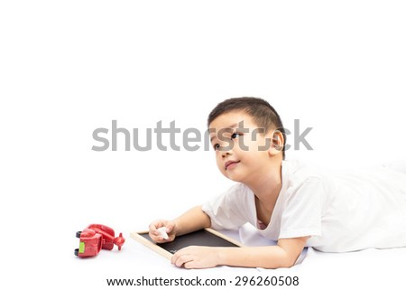Little asian boy lying with red motorcycle toy and writing on a blank blackboard isolated on white background - stock photo