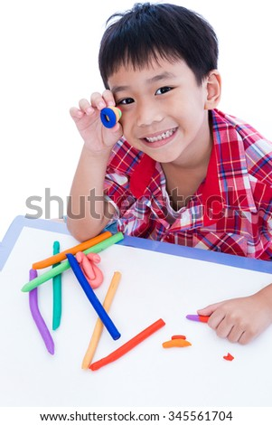 Little asian boy playing and creating toys from play dough. Child smiling and show his works from clay, over white background. Strengthen the imagination of child - stock photo
