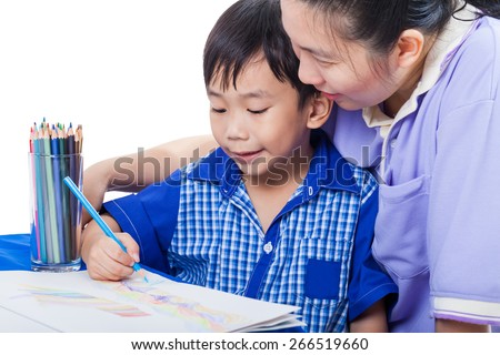 Little asian boy sitting at the table and drawing picture by colour pencil, mother teach her son. Learning, education of art and creativity concept, studio shot
