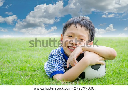Little Asian boy smiles with his football on field - stock photo