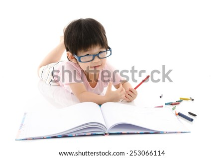 Little asian boy wearing eye glasses and writing on white background isolated - stock photo