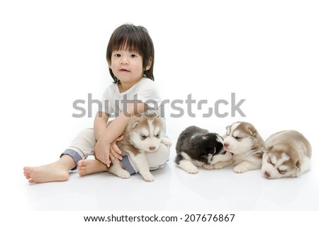 Little asian boy with puppies of siberian husky