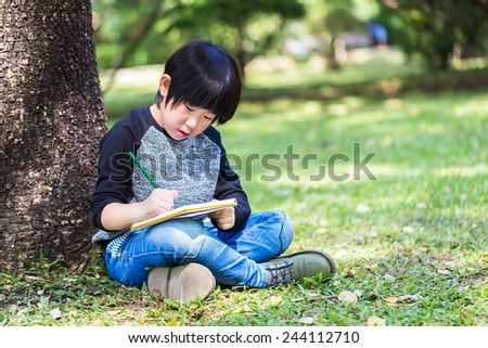 Little asian boy writing book with pencil in the park - stock photo