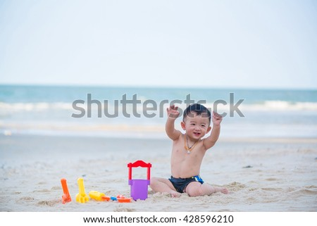 Little Asian boy 1 year old playing sand on the beach, in Thailand