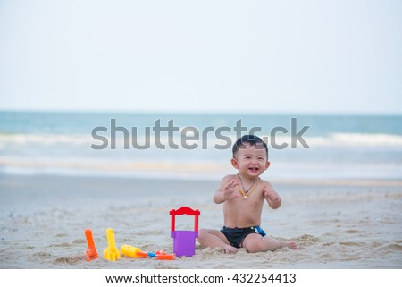 Little Asian boy 1 year old playing sand on the beach, in Thailand, shallow DOF