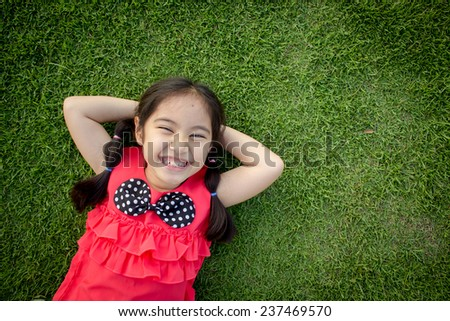 Little Asian child laying down on the grass - stock photo