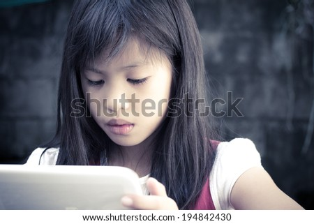 Little Asian child looks to the tablet computer
