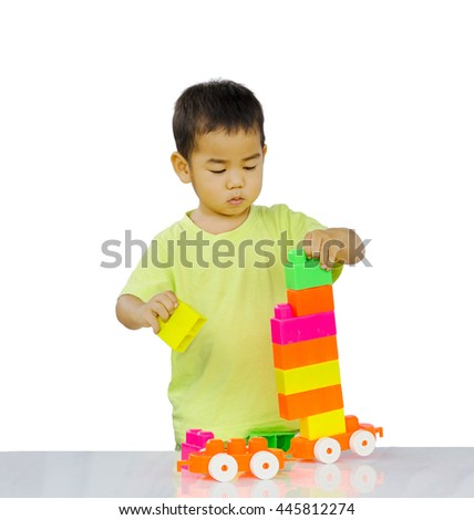 Little asian child playing with colorful construction blocks on white background isolated - stock photo
