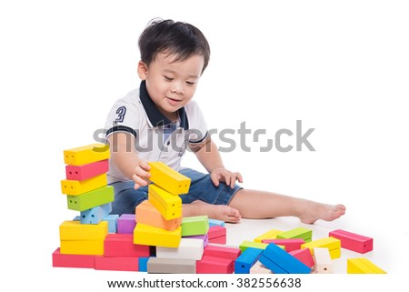 Little asian child playing with lots of colorful plastic blocks indoor. Kid boy wearing colorful shirt and having fun with building and creating. - stock photo