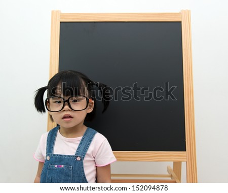 Little Asian child with big spectacles in front blackboard - stock photo