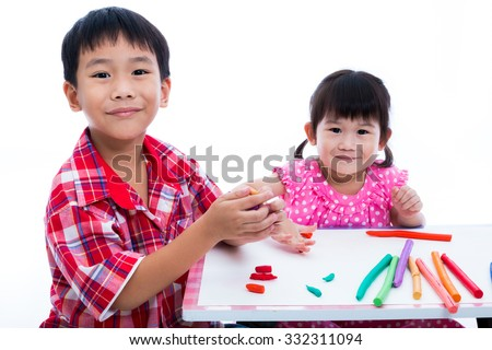 Little asian children playing and creating toys from play dough on table. Boy and girl smiling and looking at camera, on white background. Strengthen the imagination of child - stock photo