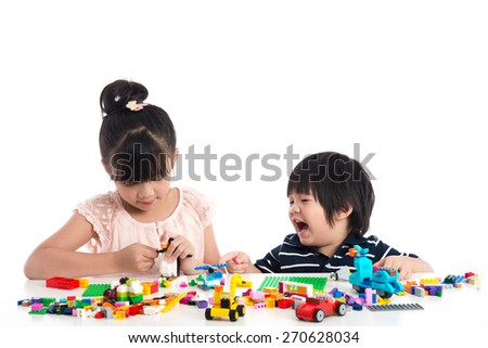 Little asian children  playing with colorful construction blocks on white background isolated - stock photo