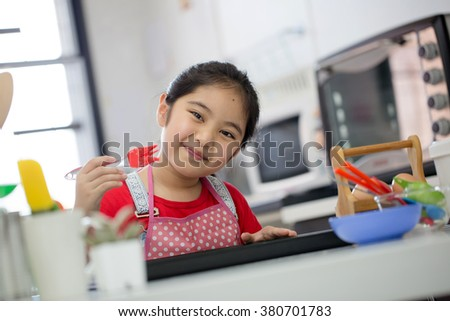 Little Asian cute chef cooking a bakery in kitchen