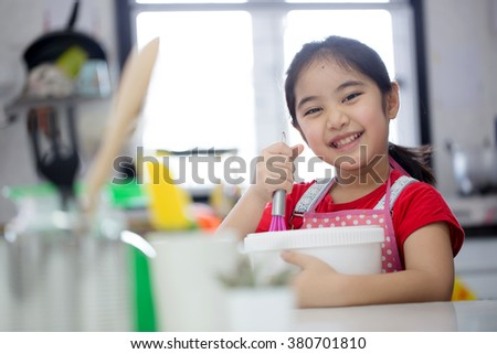 Little Asian cute chef cooking a bakery in kitchen - stock photo