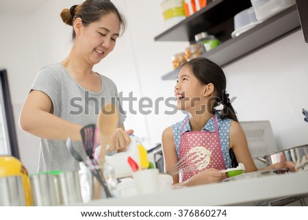 Little Asian cute chef cooking a bakery in kitchen with mother - stock photo