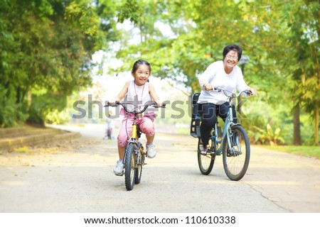 Little Asian girl and grandmother riding on bicycle with great fun - stock photo