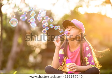 Little asian girl blowing soap bubbles outdoor at sunset - stock photo