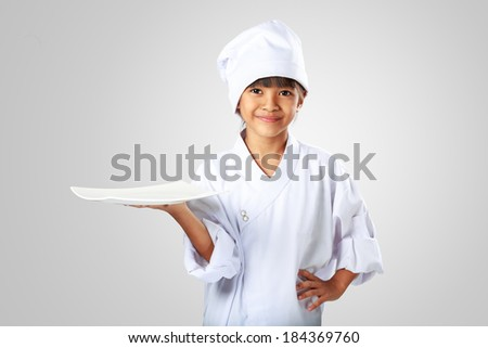 Little asian girl chef showing the empty white plate, Isolated on grey - stock photo