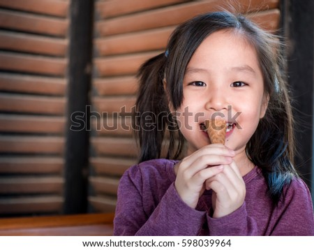 Little Asian girl eating ice cream, wood shade stripes background