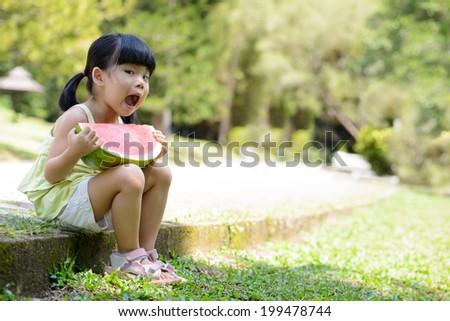 Little Asian girl eating watermelon in park - stock photo