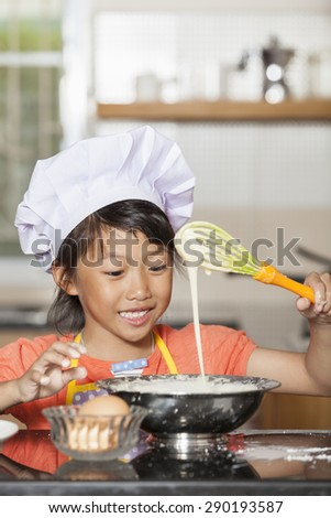 Little asian girl exciting while stir wheat flour and egg
