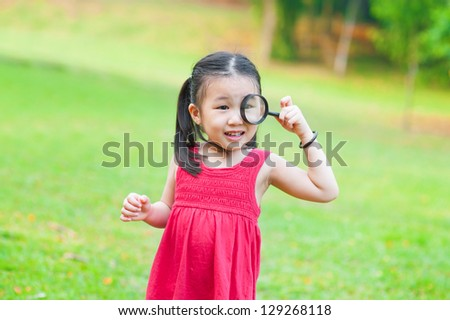 Little Asian girl exploring nature by magnifier glass - stock photo