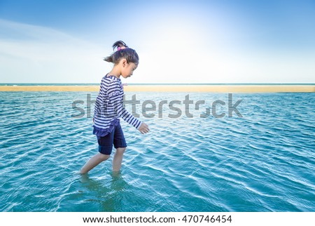 Little asian girl feeling happy and relax on the beach