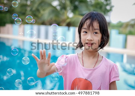Little Asian girl happy with soap bubbles.