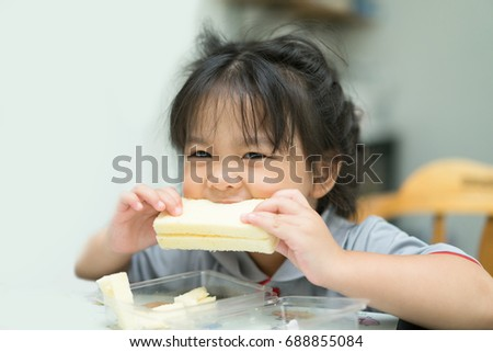 Little asian girl having breakfast in the kitchen.Little girl hungry and eating sandwich ham chess.eat and delicious face concept.