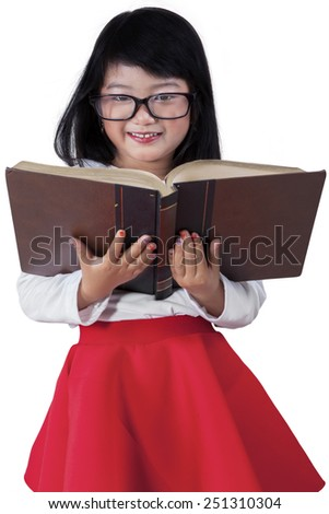 Little asian girl holding a textbook in the studio while smiling at the camera, isolated on white - stock photo