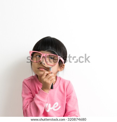 Little Asian girl holding magnifying glass in front of her eye - stock photo