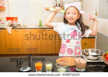 Little asian girl holding spoon and folk enjoy making tuna sandwich in kitchen, Concept of kid learning to make healthy food, Tuna sandwich ingredients preparation , - stock photo