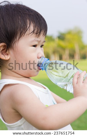Little asian girl in a white singlet drinking water from plastic bottle, after tired from a romp in the park, outdoor shot - stock photo