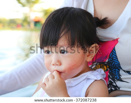 Little asian girl in mother hug at the park