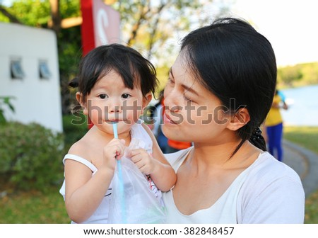Little asian girl in mother hug at the park drinking water by straw