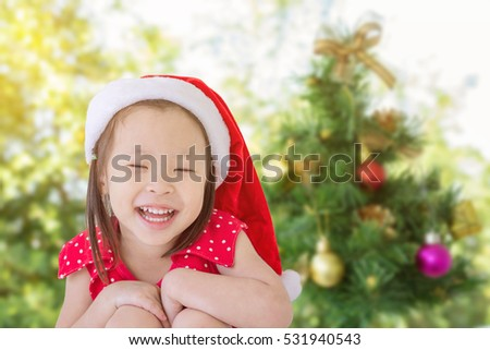 Little asian girl in santa hat smiling in front of Christmas tree