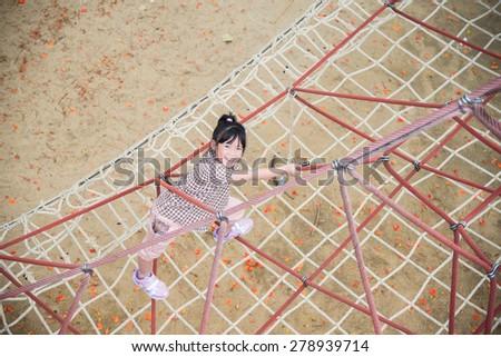 Little asian girl is having fun in adventure park - stock photo