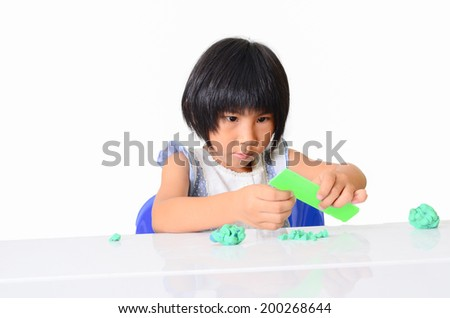 Little Asian girl is learning to use play dough in a well lit room isolated on white. - stock photo