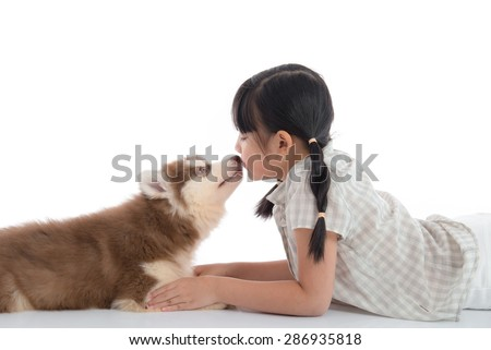 Little asian girl kissing a siberian husky puppy on white background isolated