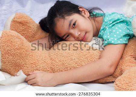 little asian girl laying on brown bear on white cotton  - stock photo