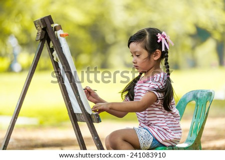 Little Asian girl painting on easel - stock photo