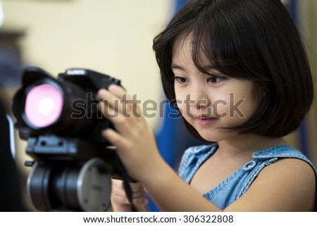 Little Asian girl photographer,looking and take the photo by your camera