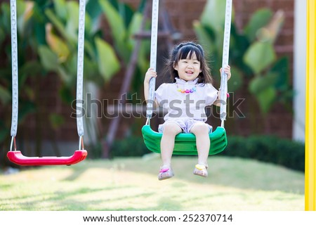 little asian girl play swing at playground - stock photo