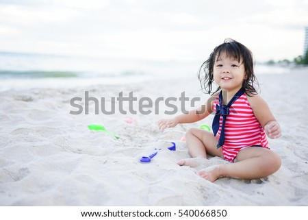 Little asian girl playing on white sand beach in Thailand.