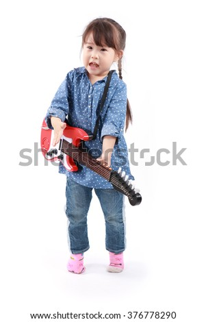 Little asian girl plays with a toy guitar on a white background - stock photo