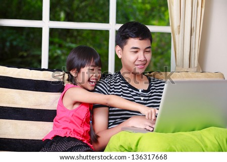 Little asian girl pointing on laptop with big brother at home - stock photo