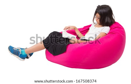Little asian girl reading a book on a pink bean bag - stock photo